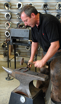 Farrier Pat Reilly shapes a horseshoe.