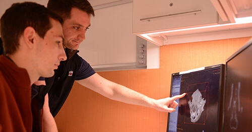 Dr. Jonathan Wood consults with radiologist Dr. Jonathan Nevins (foreground) about a 3D rendering of a CT image.
