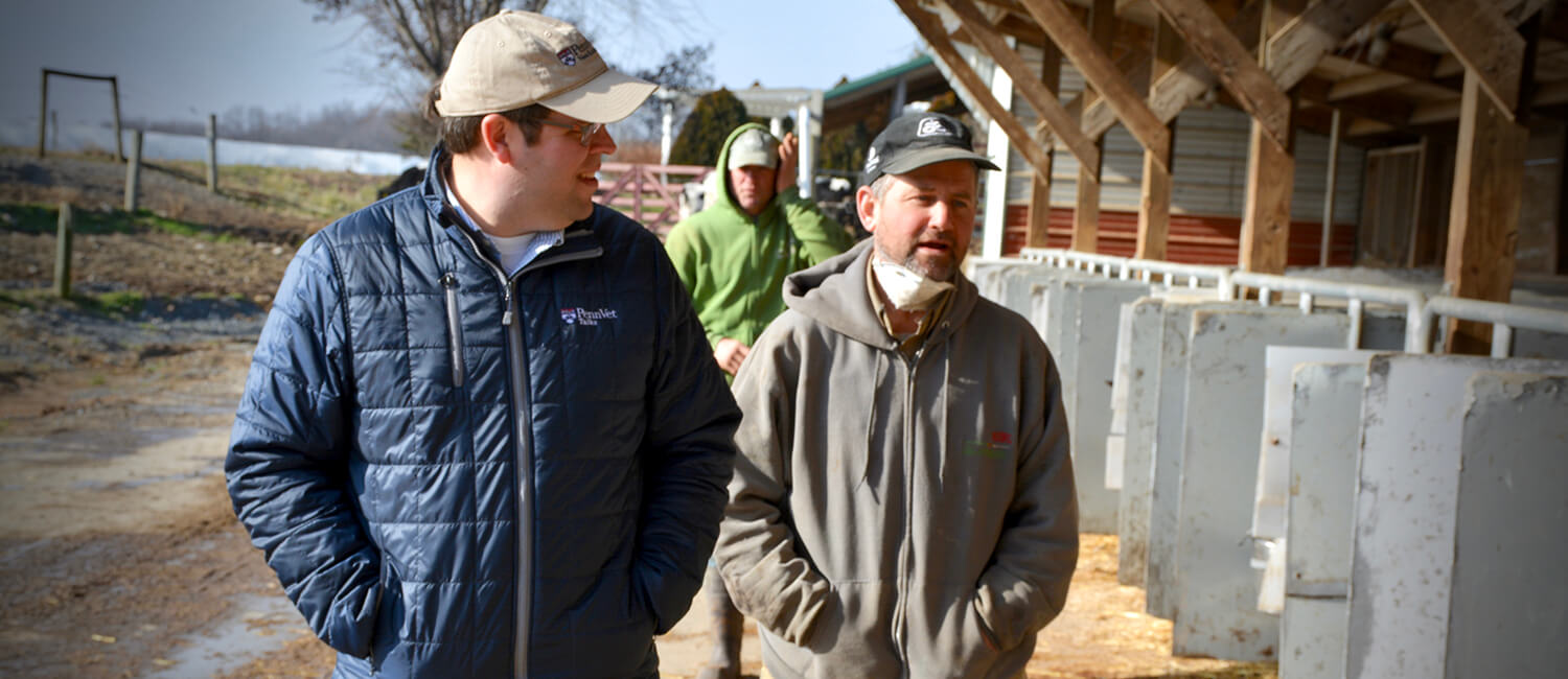 Dr. Joe Bender talks with a dairy farmer during a field visit.
