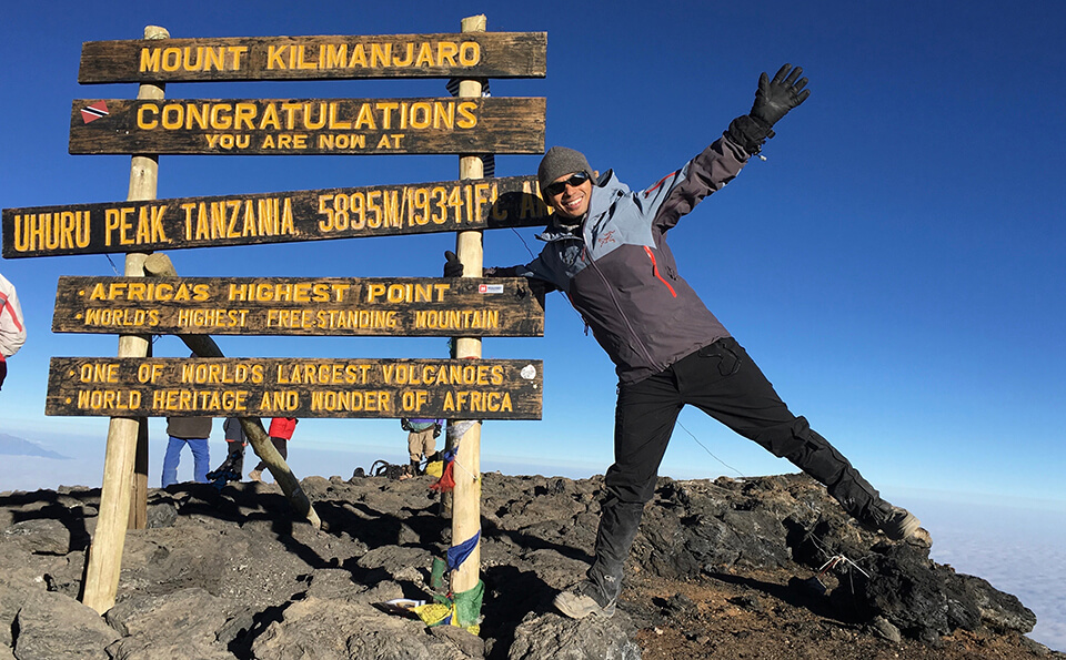 Dr. Michael Mison at the summit of Kilimanjaro in Tanzania, the highest mountain in Africa.