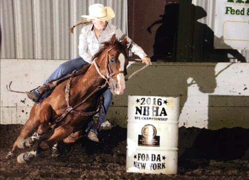 Nikki Becker rides Hammer during a barrel race.