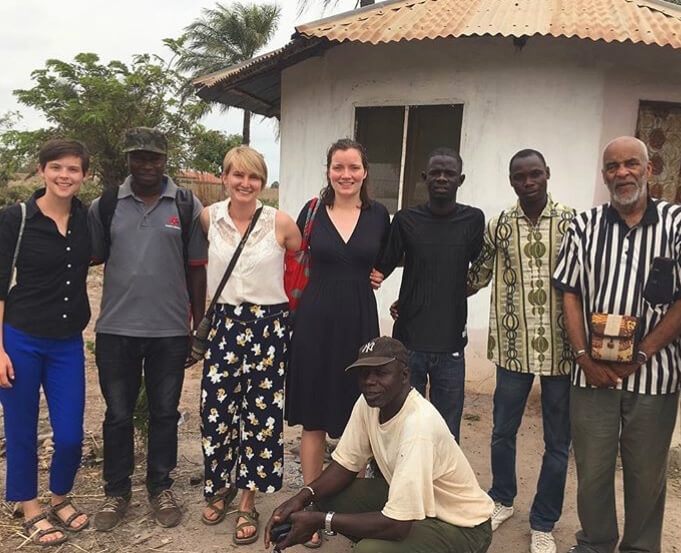 Wilson (far left), Parsons (third from left), and engineering undergraduate Madeline McGovern meet with members of the Village Development Committee of Sanyang, where the dairy will be located.