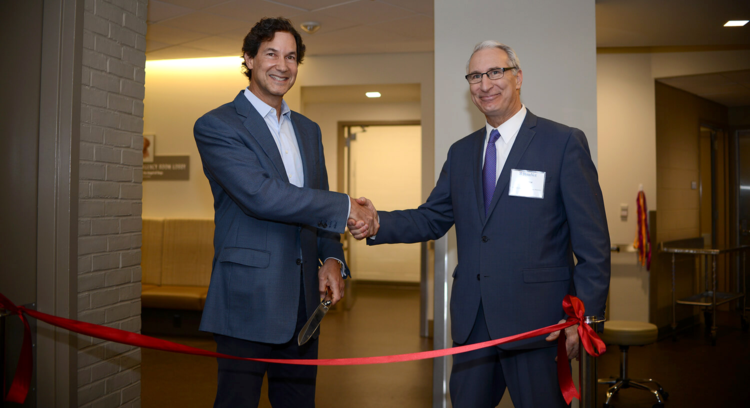 Richard Lichter and Dean Andrew Hoffman shake hands before cutting the ribbon at the dedication of the Richard Lichter Emergency Room.